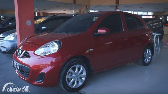 Gambar menunjukan sebuah mobil Nissan March 2017 berwarna merah dilihat dari sisi depan