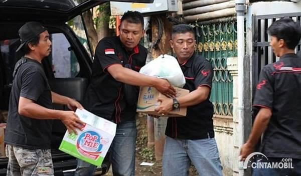 anggota Kijang Retro Indonesia membagikan bantuan korban banjir