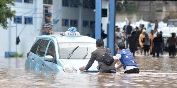 Foto karyawan Bluebird membantu memindahkan taksi saat banjir