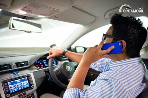 Gambar menunjukkan seorang pengemudi menggunakan ponsel saat mengemudi mobil