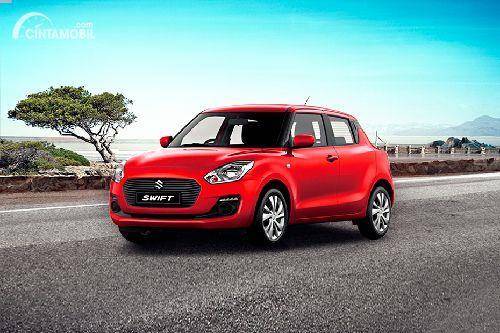 Gambar sebuah mobil Suzuki Swift berwarna merah dilihat dari sisi depan