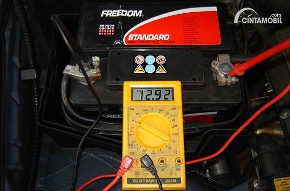 Seorang teknisi memeriksa tekanan aki mobil memakai voltmeter