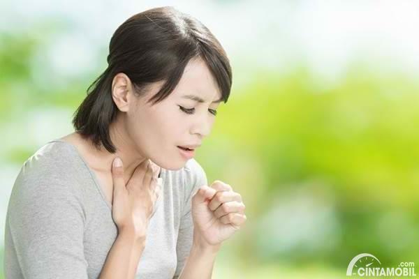 Gambar menunjukkan seorang wanita yang sedang batuk-batuk