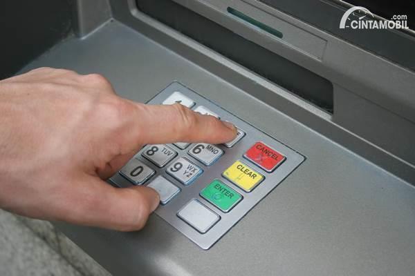Gambar seorang yang sedang tombol di mesin ATM