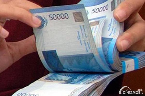 Gambar menunjukkan seorang yang sedang menghitung uang kertas