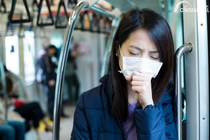 Menggunakan masker saat memakai angkutan umum