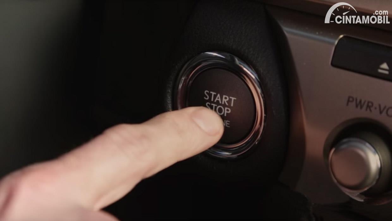 tangan yang sedang menekan tombol start stop