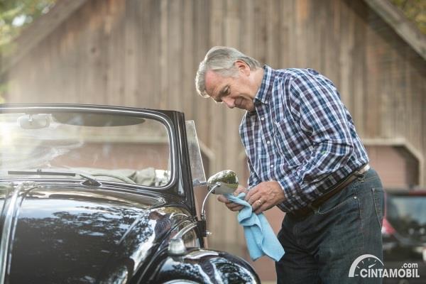 pria sedang merawat mobil klasik