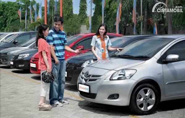 Gambar menunjukkan seorang membeli mobil bekas sedang mendengar saran dari konsultan mobil di dealer