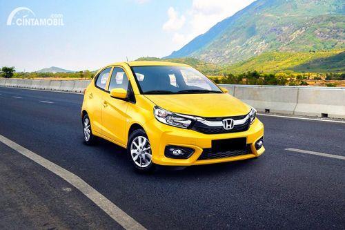 Gambar menunjukkan sebuah mobil Honda berwarna kuning dilihat dari sisi depan sedang berjalan di jalan