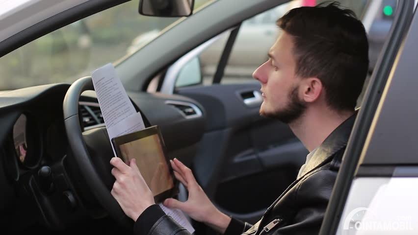 pengemudi laki-laki yang sedang menggunakan tablet pada mobil