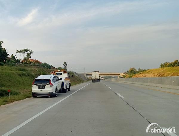 Foto menunjukkan satu unit mobil mogok dan diderek di jalan tol