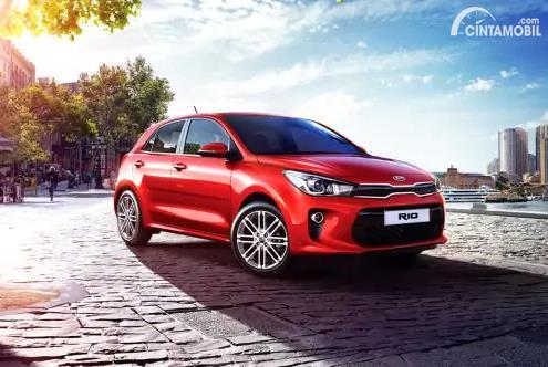 Gambar menunjukkan sebuah mobil Kia Rio berwarna merah dilihat dari sisi depan