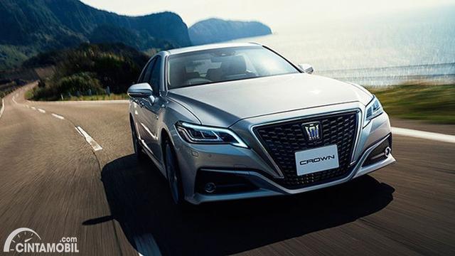 Gambar menunjukkan sebuah mobil Toyota Crown berwarna silver dilihat dari sisi depan