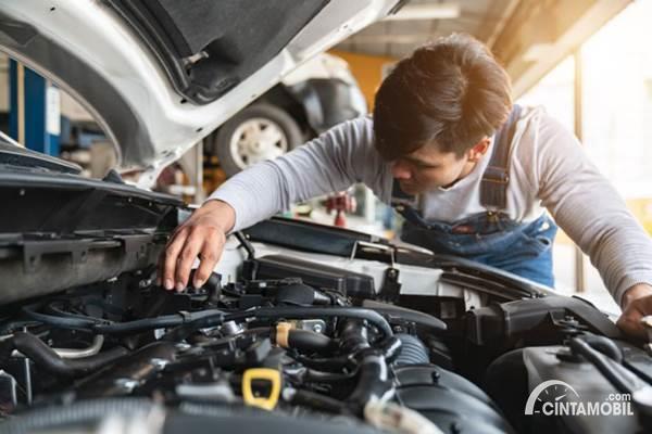 Mekanik mengecek mesin mobil