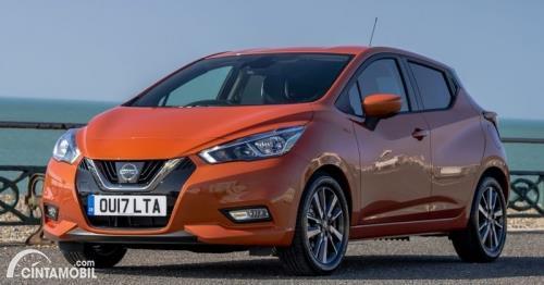 Gambar menunjukkan sebuah mobil Nissan march berwarna orange dilihat dari sisi depan
