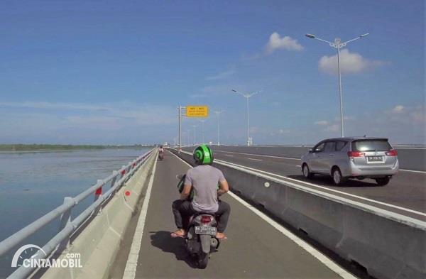 Foto menunjukkan pesepeda motor melintas di Jalan Tol Bali Mandara