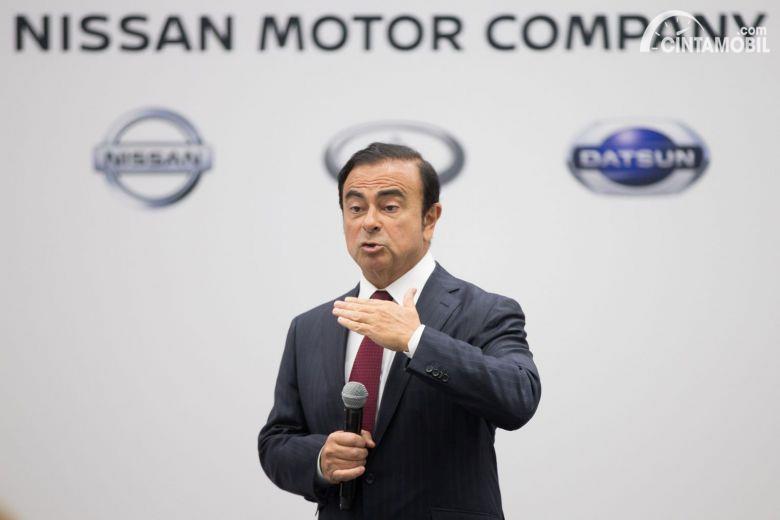 Carlos Ghosn mantan bos Nissan dengan logo Nissan di belakang