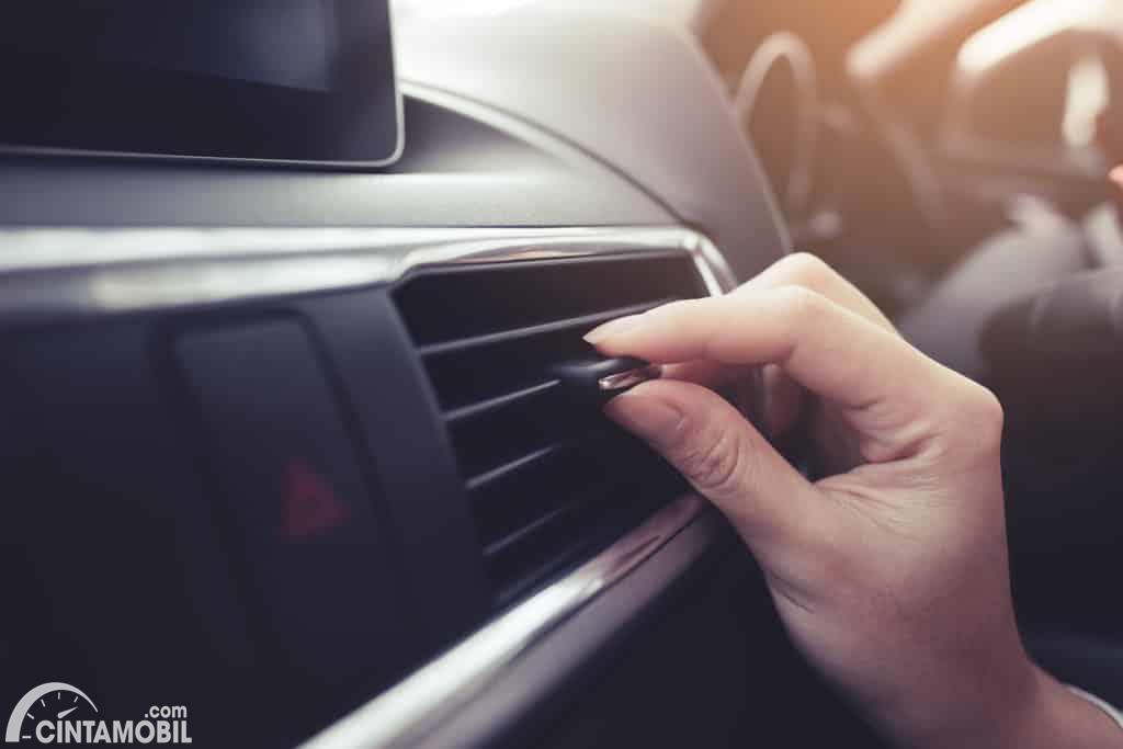 tangan yang sedang mengecek AC mobil