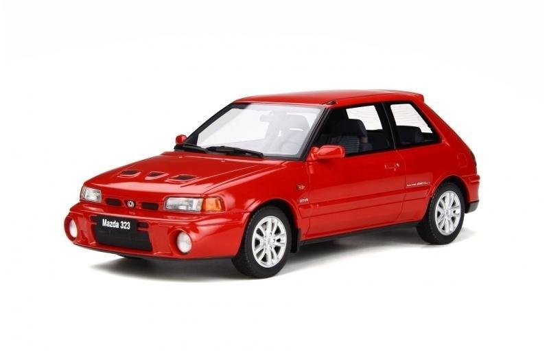 Gambar menunjukkan sebuah mobil Mazda 323 berwarna merah dilihat dari sisi depan
