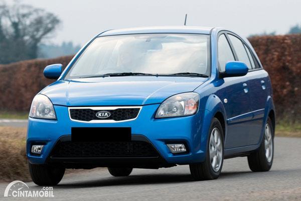 Gambar sebuah mobil Kia Pride berwarna biru dilihat dari sisi depan