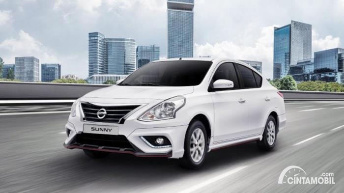 Gambar menunjukkan sebuah mobil Nissan Sunny berwarna silver dilihat dari sisi depan sedang berjalan di jalan Indonesia