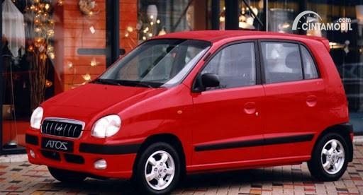 Gambar menunjukkan sebuah mobil Hyundai Atoz 2000 berwarna merah dilihat dari sisi depan
