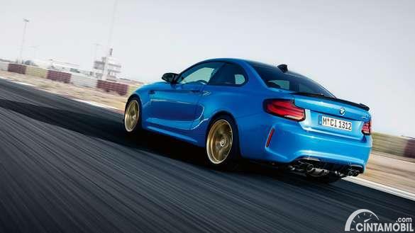 Gambar menunjukkan tampilan mobil BMW M2 berwarna biru dilihat dari sisi belakangnya