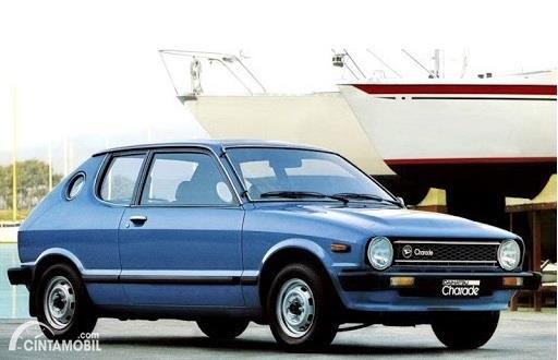 Gambar menunjukkan tampilan mobil Daihatsu Charade berwarna biru dilihat dari sisi depan