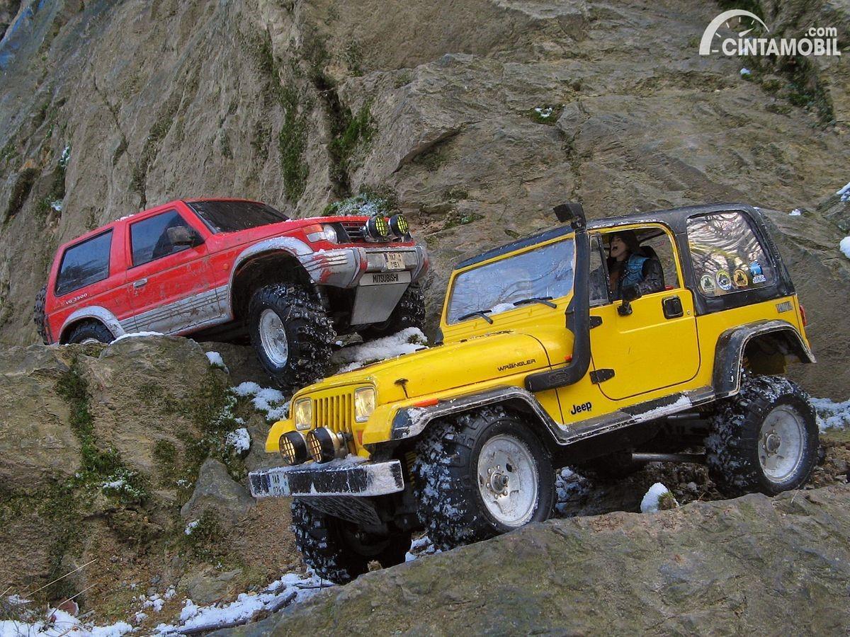 Gambar sebuah mobil Jeep Wrangler YJ berwarna kuning dilihat dari sisi depan
