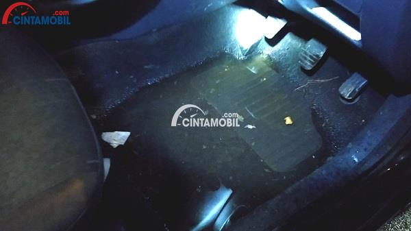 Gambar yang memperlihatkan karpet kaki pada mobil basah dan lembab