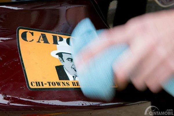 Gambar yang menunjukan pengemudi yang membersihkan stiker