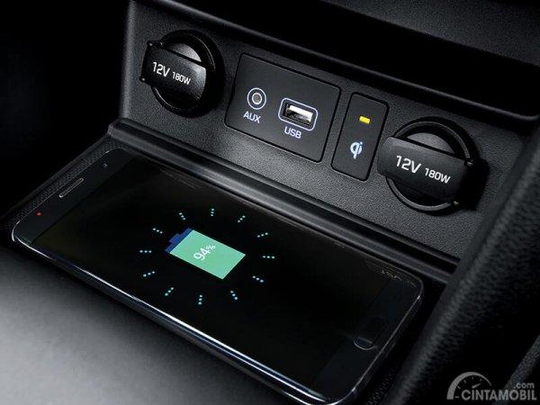 Tampak sebuah ponsel sedang diletakkan pada wireless charging pada mobil