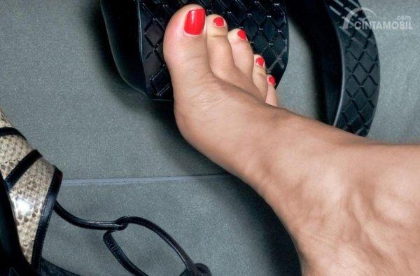 Gambar yang menunjukan pengemudi wanita yang berkendara tanpa alas kaki