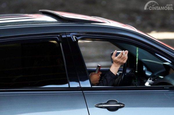 Gambar yang menunjukan pengemudi yang membuka jendela ketika merokok