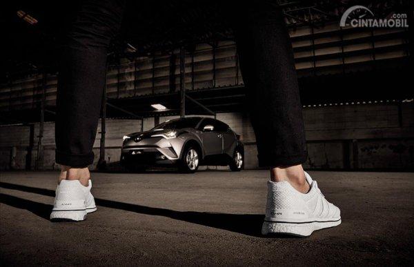 Tampak sebuah sepatu Adidas CH-R dan mobil Toyota CH-R di depannya