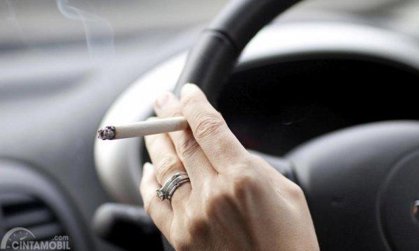 Foto seorang merokok sambil mengemudi