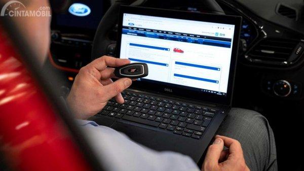 teknisi dengan laptop yang memegang kunci fob Ford