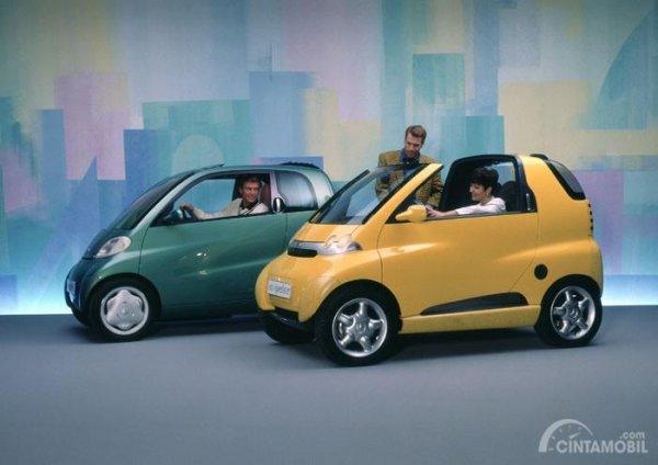 Gambar menunjukkan dua mobil Smart Concept 1993 berwarna kuning dan hijau dilihat dari sisi depan