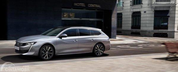 Gambar sebuah mobil All New Peugeot 508 SW 2019 berwarna silver dilihat dari sisi samping sedang parkir di depan halaman rumah