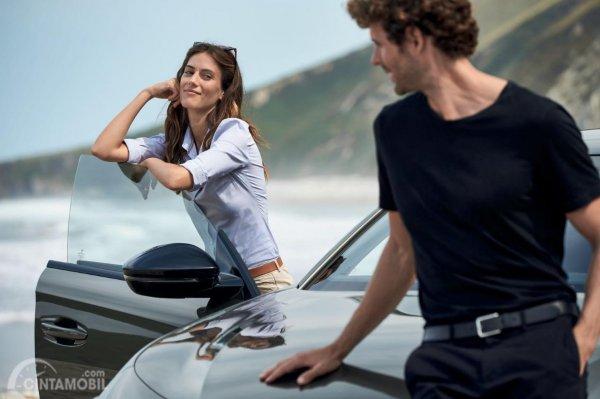 Gambar seorang laki-laki dan seorang perempuan sedang memfoto di dekat Frameless door dari mobil All New Peugeot 508 SW 2019