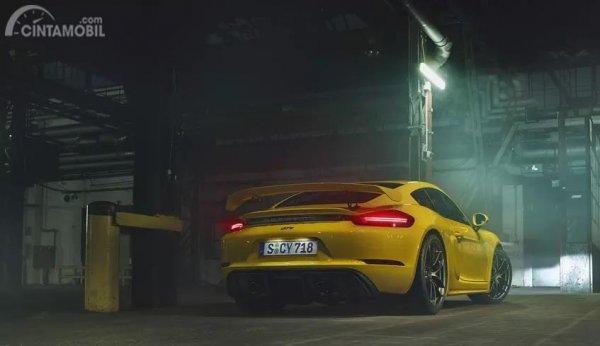 Foto sebuah mobil Porsche 718 Cayman GT4 2019 berwarna kuning dilihat dari sisi belakang
