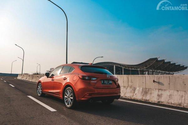 gambar sebuah mobil Mazda 3 2017 berwarna merah dilihat dari sisi belakang