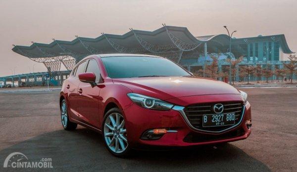 gambar sebuah mobil Mazda 3 2017 berwarna merah dilihat dari sisi depan