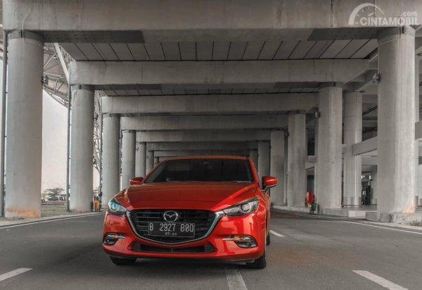 gambar sebuah mobil  Mazda 3 2017 berwarna orange dilihat dari sisi depan