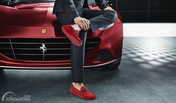 Sepatu berwarna merah dengan mobil Ferrari
