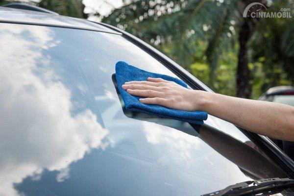 Foto menunjukkan seseorang sedang mengelap kaca mobil menggunakan kain lap microfiber
