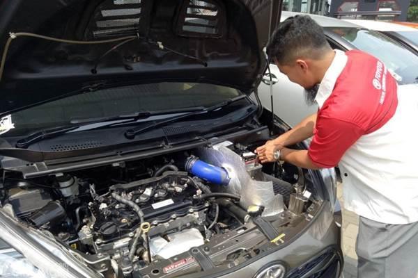 seorang sedang cek dan merawat mesin mobil