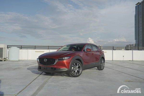 mobil baru Mazda CX-30 berwarna merah di atas gedung