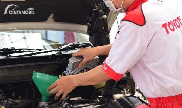teknisi sedang mengganti oli mesin Toyota Avanza